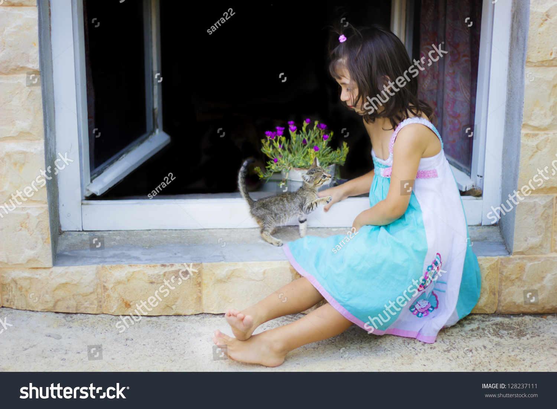 可爱的小女孩和小猫玩了窗口