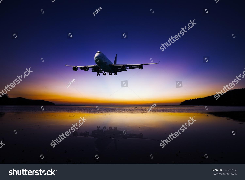 飞机飞行在热带多彩的晚上天空大海与反射美丽的日落