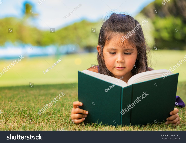 可爱的小女孩之外的书在草地上阅读