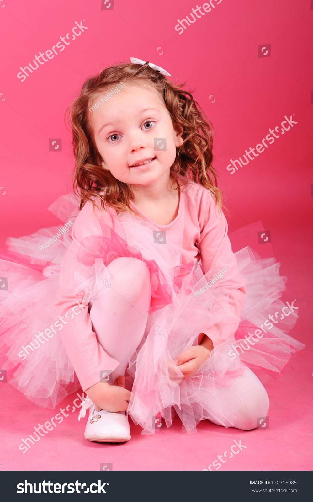 微笑的可爱女孩坐在粉红色背景