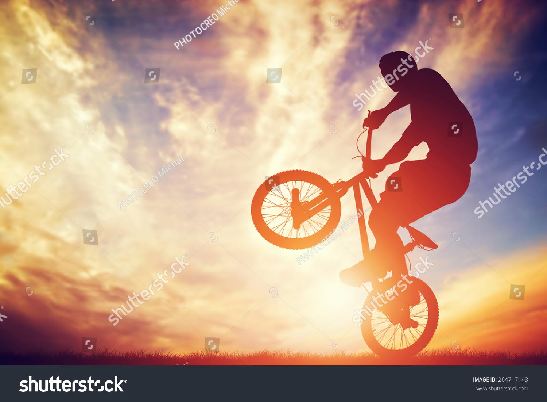 男子骑着自行车在落日的天空戏法表演