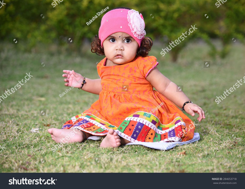 可爱的小女孩坐在绿草